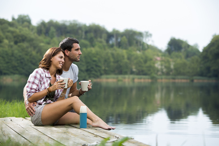 Relaxed young couple with coffee mugs sitting on a jetty at lake looking at distance LANG_EVOIMAGES