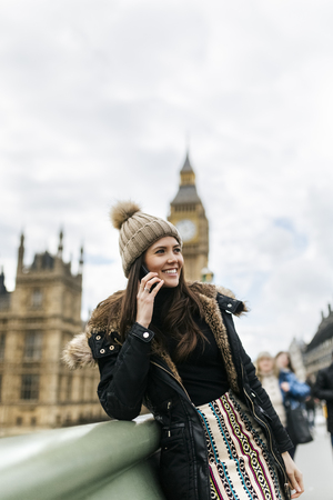 UK, London, happy young woman telephoning with smartphone in front of Palace of Westminster LANG_EVOIMAGES