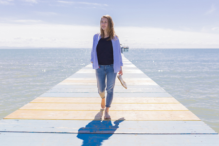 Young woman walking on jetty LANG_EVOIMAGES