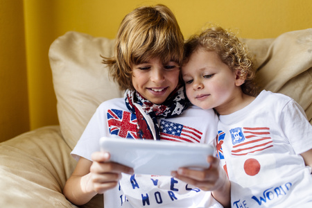 Portrait of two boys sitting on couch using digital tablet