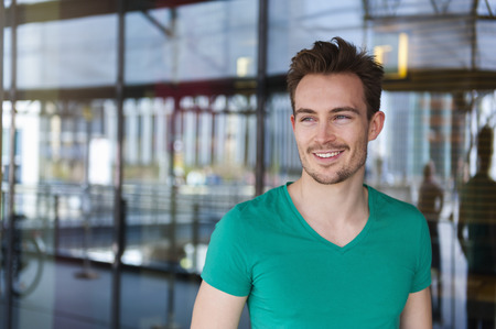 Portrait of smiling young man with stubble standing in front of glass facade