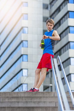Young sporty man with water bottle and smartwatch LANG_EVOIMAGES
