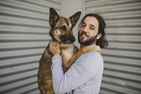 Portrait of young man holding dog