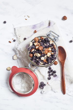 Preserving jar of overnight oats with pineapple, coconut, chia pudding, hazelnuts and berries