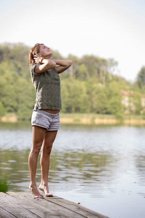 Young woman stretching on a jetty at lake in the morning