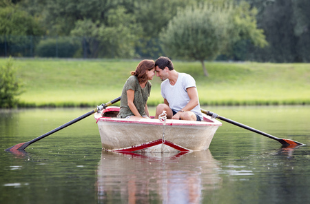 Young couple face to face in a rowing boat on lake LANG_EVOIMAGES