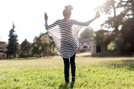 Woman dancing on a meadow while hearing music with earphones