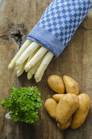 White asparagus, potatoes and parsley on wood