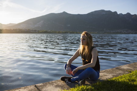 Italy, Lecco, thoughtful teenage girl sitting on the edge of the lake