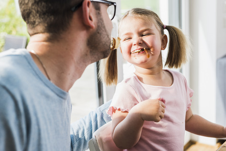 Playful father and daughter with food in mouth LANG_EVOIMAGES