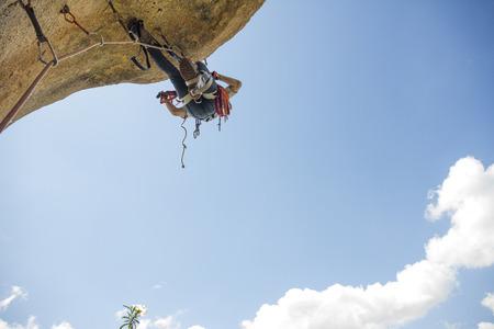 Climber climbing a rock using aid climbing techniques LANG_EVOIMAGES