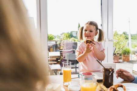 Girl with family at breakfast table