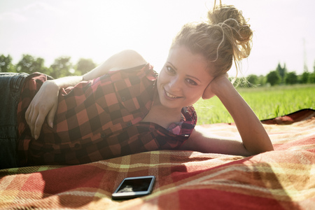 Portrait os smiling woman lying on blanket on a meadow LANG_EVOIMAGES