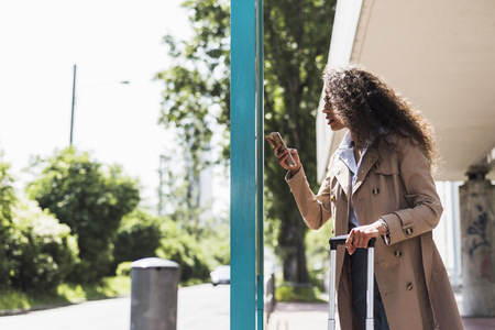Young woman with luggage and cell phone at bus stop