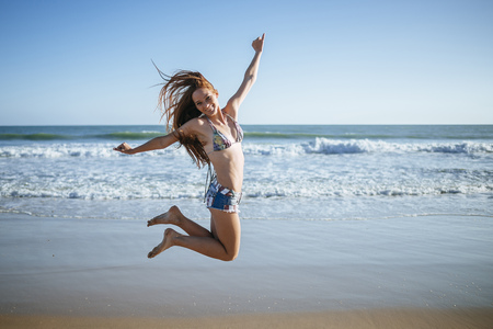 Enthusiastic young woman jumping on beach LANG_EVOIMAGES