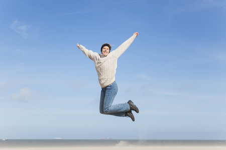 Enthusiastic mature woman jumping on beach