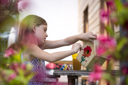 Girl painting red flower on a birdhouse LANG_EVOIMAGES