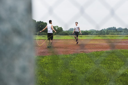 Two athletes skipping rope on sports field