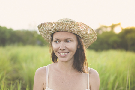 Portrait of smiling woman wearing summer hat in nature