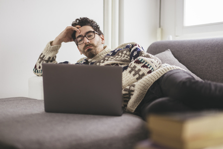 Man lying on a couch looking at laptop