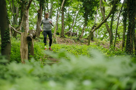 Young man exercising in forest LANG_EVOIMAGES