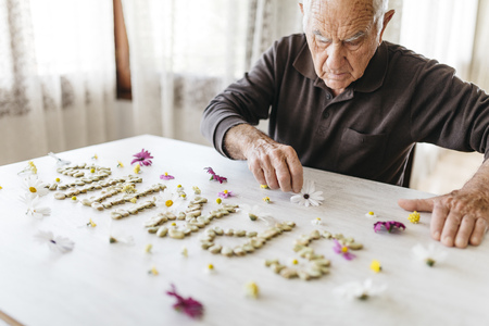Senior man shaping the word spring with dried beans surrounded by flowers on a table
