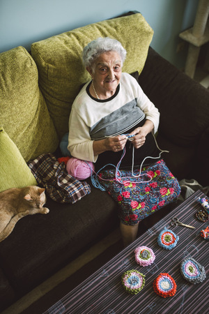 Portrait of crocheting senior woman sitting on couch beside her sleeping cat LANG_EVOIMAGES