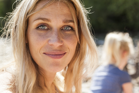 Portrait of smiling blond woman with freckles