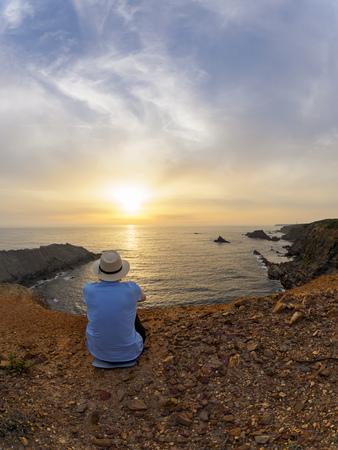 Portugal, Senior man sitting at bay watching sunset LANG_EVOIMAGES