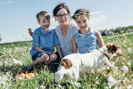 Happy mother and two children with dog in meadow