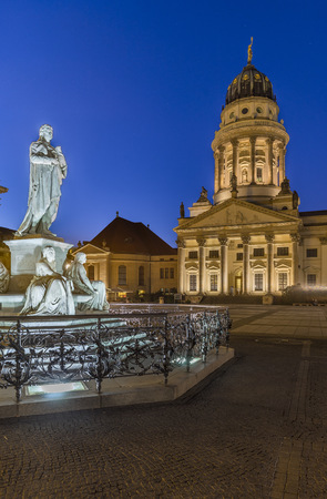 Germany, Berlin, lighted French Cathedral and statue of Friedrich Schiller at Gendarmenmarkt