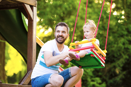 Portrait of happy father with his little daughter sitting on a swing of playground LANG_EVOIMAGES