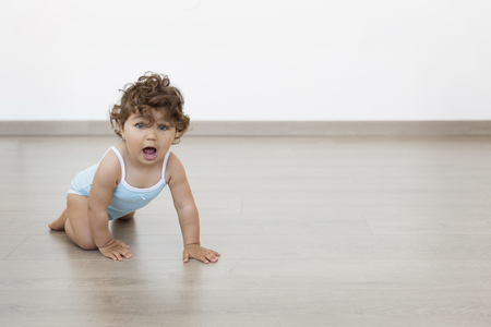 Baby girl crawling on floor lwith her mouth wide open