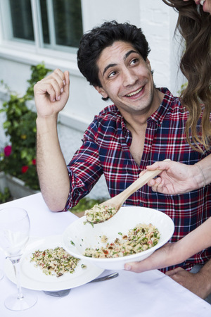 Woman serving tabbouleh to her guest during a summer dinner