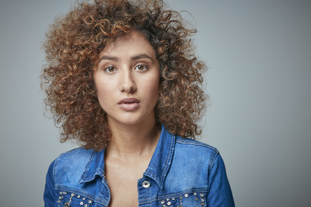 Portrait of astonished redheaded woman with curly hair LANG_EVOIMAGES