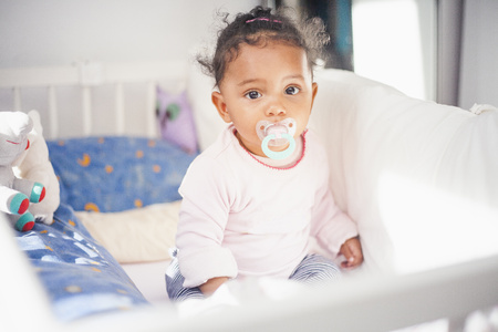 Portrait of tired baby girl with pacifier sitting in cot LANG_EVOIMAGES