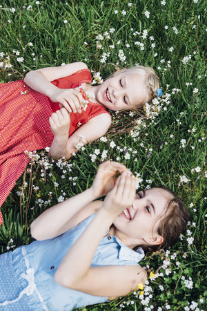 Two happy girls lying in flower meadow LANG_EVOIMAGES