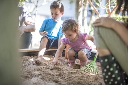 Girl with family playing in sandpit