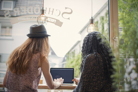 Two young women using laptop in a cafe