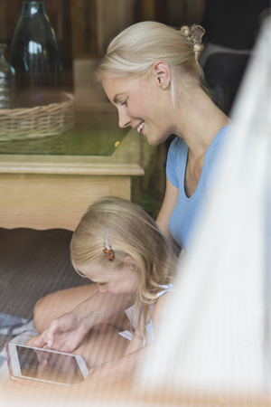 Mother and little daughter sitting behind window pane looking together at tablet