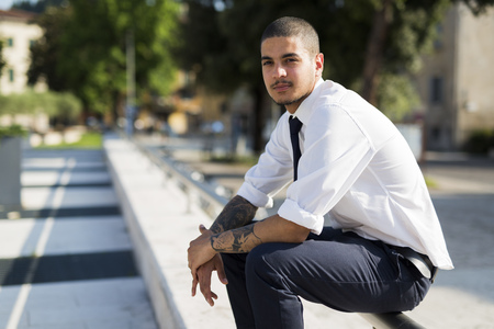 Portrait of young businessman with tatoos on his forearms sitting on railing LANG_EVOIMAGES