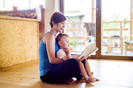 Pregnant mother looking at picture book with her little son