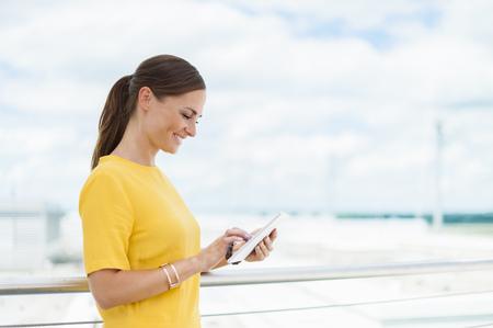 Smiling brunette woman looking at digital tablet