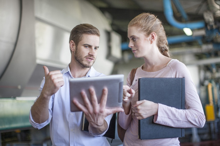 Businessman and woman discussing work, using digital tablet LANG_EVOIMAGES
