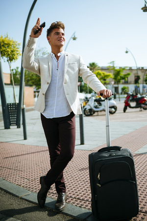 Young man with suitcase hailing a taxi
