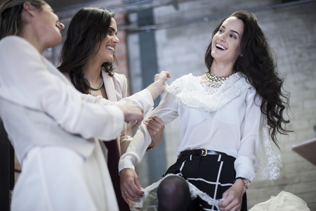 Happy dressmakers with client trying on wedding dress LANG_EVOIMAGES