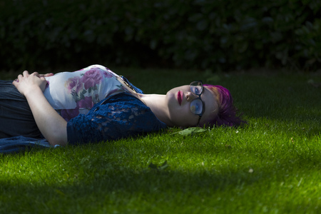 Portrait of relaxed young woman with dyed hair lying on a meadow