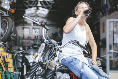 Young woman drinking beer from bottle on motorbike LANG_EVOIMAGES