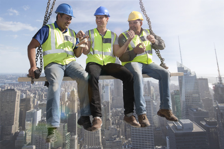 Three construction workers sitting on suspended scaffolding high above city having lunch LANG_EVOIMAGES