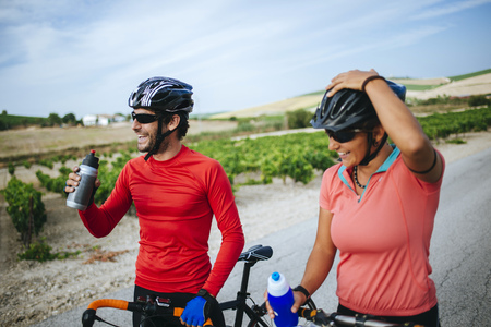 Spain, Andalusia, Jerez de la Frontera, couple of bikers drinking water on a rural road between vineyards